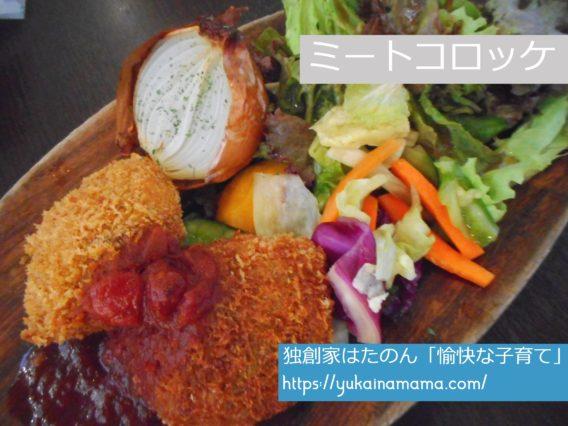 丸ごと玉ねぎやカラフルな野菜が添えられた二つのミートコロッケ