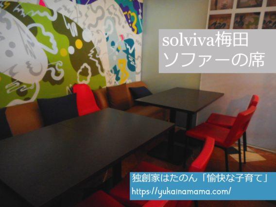 カラフルな絵の描かれた壁があるSOLVIVA梅田ソファー席
