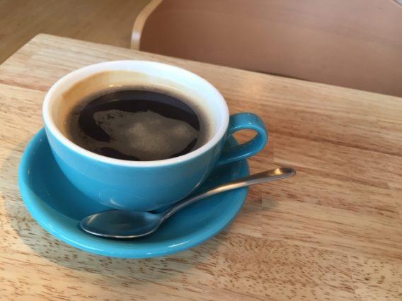 お洒落な机と青いコップに入ったコーヒー